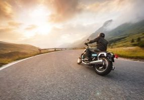 Motorcycle driver riding in Dolomite pass, Italy, south Europe.
