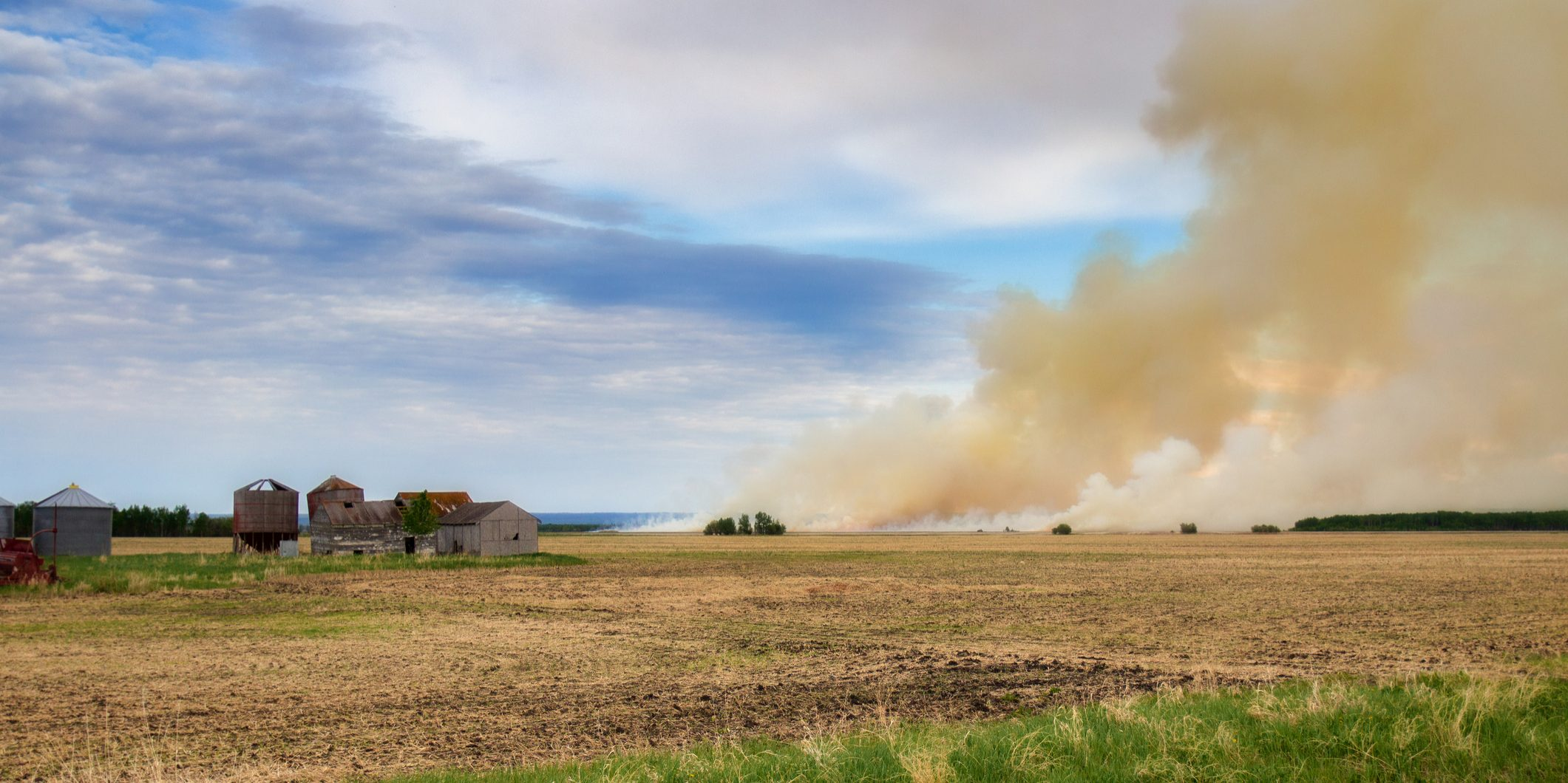 Billowing clouds of smoke from a fire burning a farm field with old sheds nearby in a summer landscape